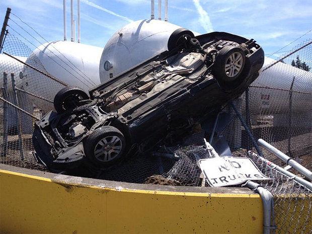 photo of car upside down near propane tanks